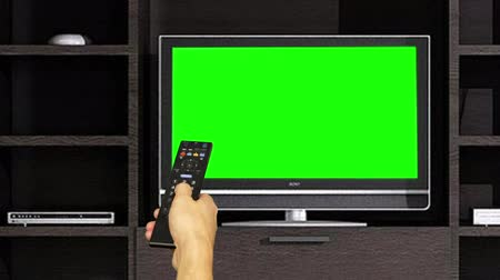 ladění : Hand using remote control for switching TV channels on green screen background