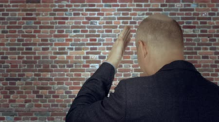 ludzik : Adult man knocking hand on forehead back view on brick wall background