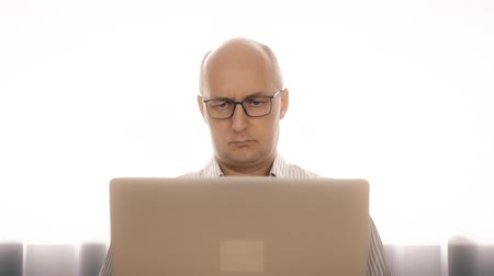 unrest : Sadness man in glasses working on notebook and rubbing eyes from fatigue Stock Footage