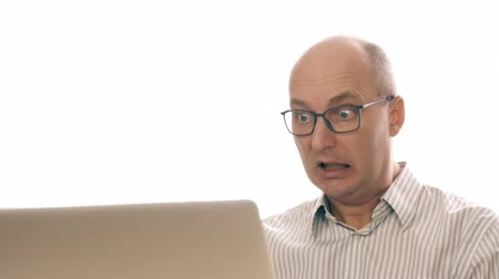 mračící : Portrait of a business man in glasses, with frightened look, sitting at laptop in office. Frightenedly wipes himself in screen, into tell because he feels fear. Close up.