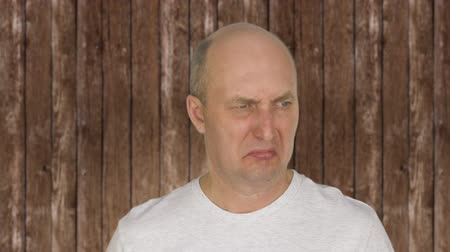 bad mood : Portrait of bald middle aged man feeling disgust Stock Footage