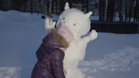 falu : Happy little girl hugging snowman on evening winter walking in country village