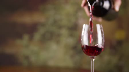 şarap kadehi : Close up male hand pouring red wine in glass from bottle slow motion