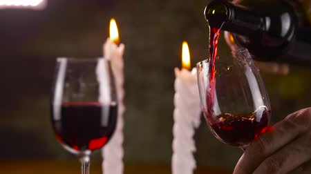 şarap kadehi : Male hand pouring red wine in glass from bottle on candle background Stok Video