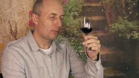 şarap kadehi : Man winemaker drinking red wine from glass. Man sommelier tasting wine close up. Show thumbs up ok sign gesture.