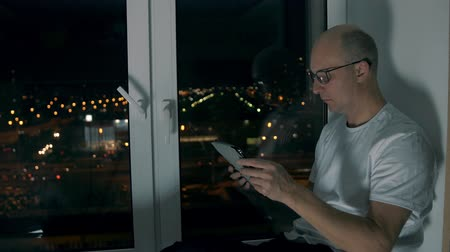 кавказский : Middle aged man in eyeglasses reading e-book and sitting on windowsill at night