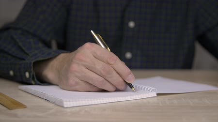 memo : Man studying and writing in copybook with pen. Close up man hand with pen write down thoughts into notebook. Stock Footage