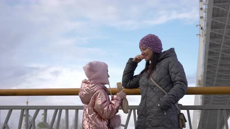 párek v rohlíku : Happy daughter eating hot dog and talking with mother in city in winter Dostupné videozáznamy