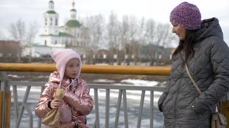 хот дог : Little daughter eating yummy hot dog and talking with mother in winter Стоковые видеозаписи