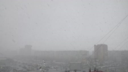 snowy background : Blizzard or snowfall in urban city with buildings and cars in winter Stock Footage