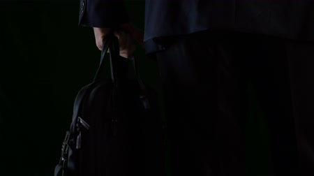 go away : Business man holding briefcase in hand and going away in darkness Stock Footage