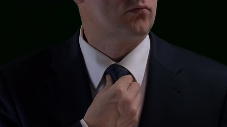 gravata : Close up portrait business man correcting tie and looking into camera Stock Footage