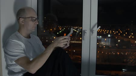 sill : Bald man in glasses looking tablet pc sitting on windowsill with night cityscape