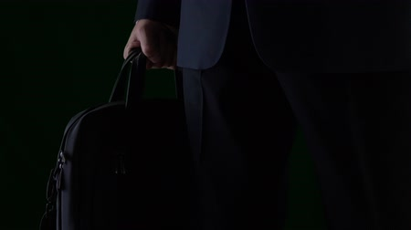 batoh : Male hand holding business briefcase isolated on black background close up
