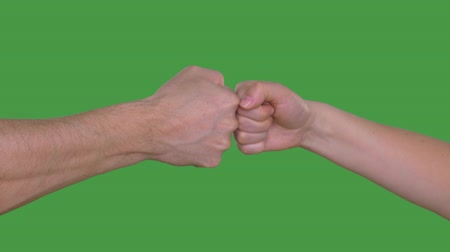 tenso : One fist beating another fist isolated on green background. Alpha channel, keyed green screen Vídeos