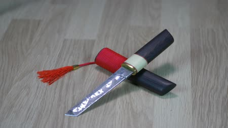 dýka : Japanese tanto knife with scabbard for samurai lying on wooden background. Track focus DOF.