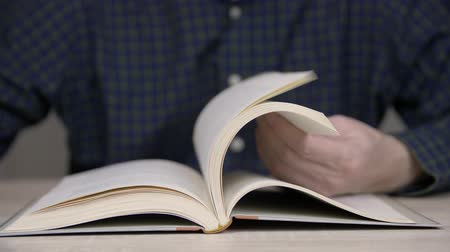 bookshop : Man flipping pages in book for browsing close upf. Browsing pages in book Stock Footage