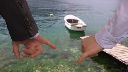 desgaste : Couple holding with little fingers, boat and wooden pier on lake Stock Footage