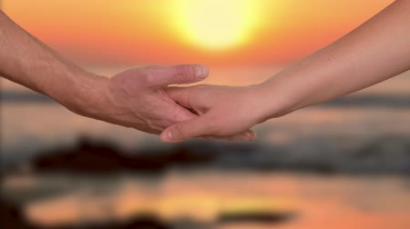 parceiro : Tender woman puting palm upper mans hand with sunset over ocean on background Stock Footage