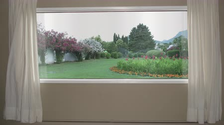 locsolás : View from the window to beautiful garden with lawn, flowers and automatic sprinkler system. Background Plate, Chroma Key Video Background Stock mozgókép