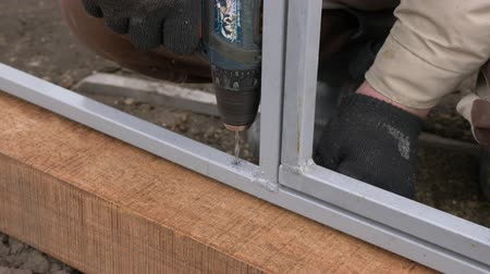 broca : Close up of constructor in gloves drilling hole in wooden frame