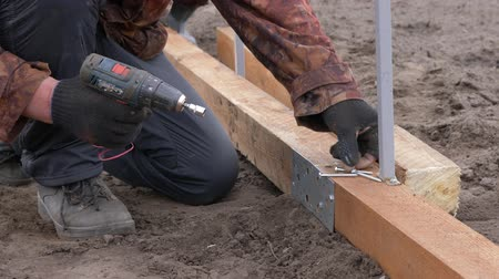 parafusos : Builder working with electric screwdriver and wooden frame on construction Vídeos