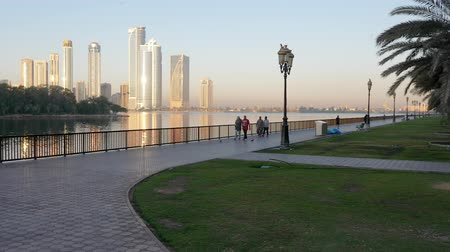 emirados : Sharjah, UAE - May 10, 2018: arab people walking on morning embankment on background reflected sunlight in glass skyscrapers. City embankment and park in Sharjah city in UAE.