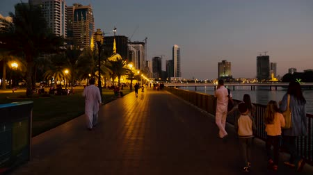 corniche : Sharjah, UAE - May 10, 2018: european tourists with childrens walking on evening embankment Al Buheirah Corniche past Khalid lake on background skyscrapers in Sharjah city in UAE.