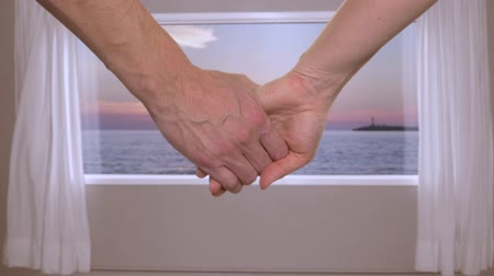 kurtyna : Couple holding hands together in room with beautiful sunset over the sea outside the window