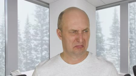 łysy : Face disgusted man with dislike on background window with view on snowfall in forest Wideo