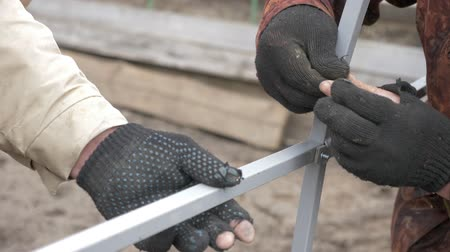 parafusos : Male hand in gloves tightens bolt metal construction outdoor close up