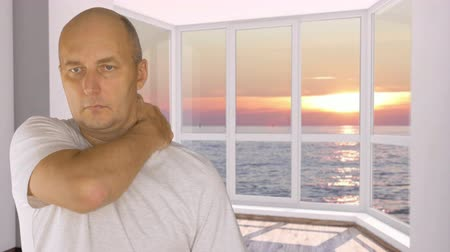 masaż twarzy : Man on background window with view on evening sunset doing himself shoulder massage Wideo