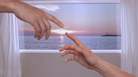 ruhanilik : Male forefinger touching with female fingers as Michelangelo on background window with view on evening sunset in sea