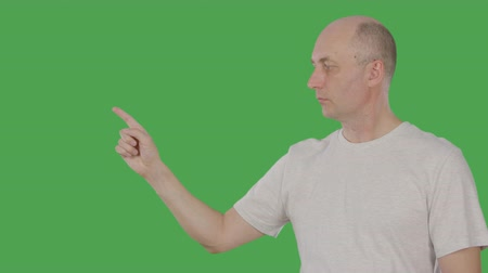 forefinger : Caucasian man pointing forefinger for showing or presenting something isolated on green background. 1 2 3 point. Alpha channel, keyed green screen