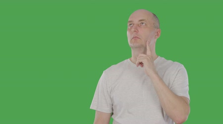 tenso : Bald man thinking and touching his chin with finger and inventing original idea. Alpha channel, keyed green screen