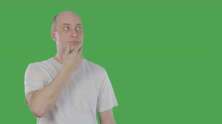 tenso : Emotional man thinking, guessing and pointing up with idea. Alphachannel, keyed green screen