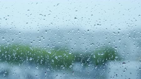 nemli : Raindrops on transparent window glass during rain on blurred background Stok Video