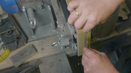 tření : Male hand sharpening knife with bright sparks on professional grinder lathe
