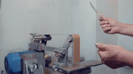 emery : Male hand holding knife blade after sharpening on professional grinder lathe