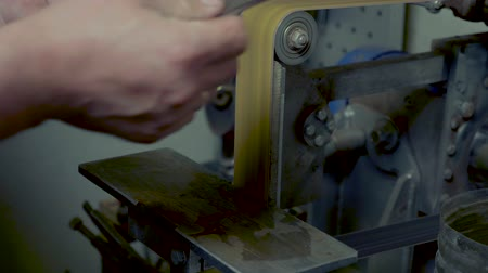 workman : Diy man grinding metal knife with sparks on grinder in workshop Stock Footage