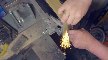 keskin : Workman making knife blade with sparks on abrasive machine, do it yourself, high angle view