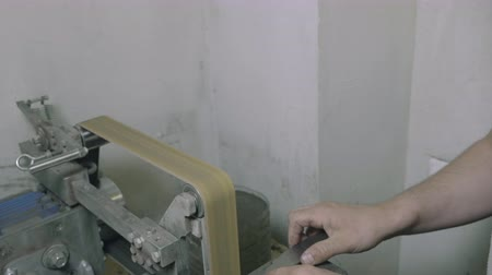 őrlés : Diy man looking at metal knife and grinding it on abrasive machine, partial view