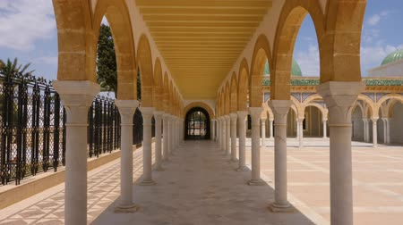 cami : Colonnade with arches on territory mausoleum Habib Bourguiba in Monastir city. Track in shot sunny day