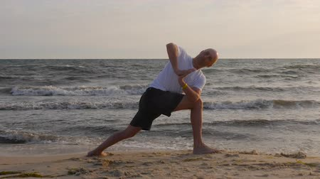 jimnastik : Adult man training yoga asana on sea beach. Man practising yoga pose outdoor