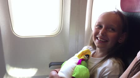 dinlenmek : Happy girl with pillow sitting on chair in cabin airplane and laughing while fly Stok Video