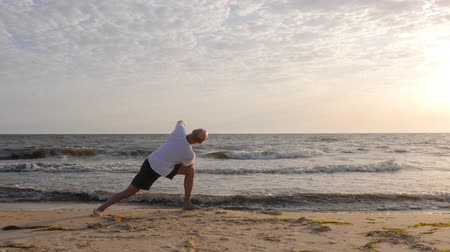 ruhanilik : Sportive man practicing yoga asana on seashore at sunset