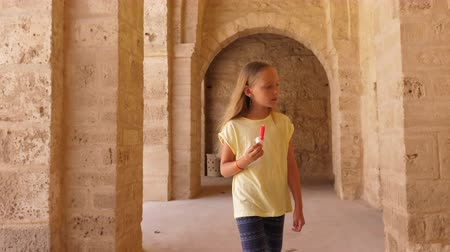 tunisia : Young girl walking and eating ice-cream on background with arch from beige stones
