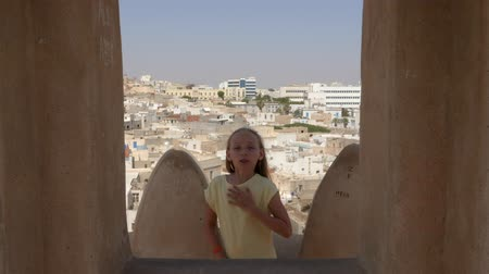 piada : Young girl dancing joking dance against arabian town on background