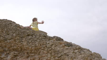 arqueologia : Girl teenager sitting on rocky stairs and waving hand while travel Stock Footage