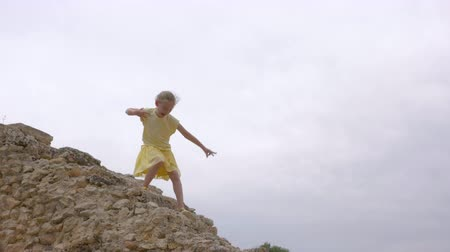 żart : Funny teenager girl walking down on ancient stairs of rock Wideo